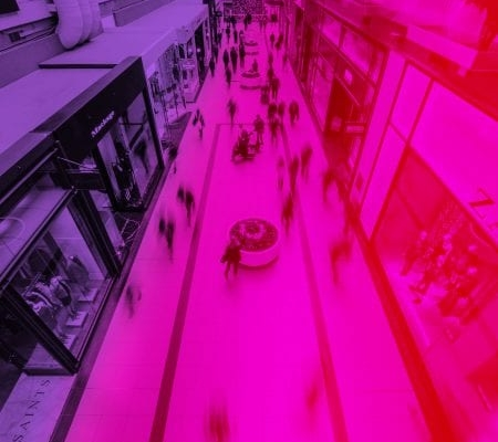 a busy shopping street visualized a bit blurry with a pink overlay